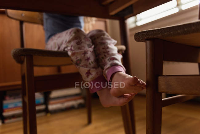 Low section of little girl sitting on chair at home — Stock Photo