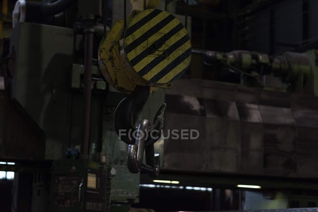 Hook of crane lifting metal equipment in metal industry — Stock Photo