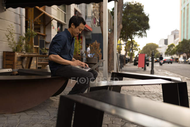 Concentrated Asian businessman using laptop in pavement cafe — Stock Photo