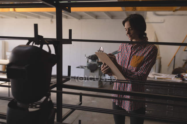 Female welder writing on clipboard in workshop. — Stock Photo