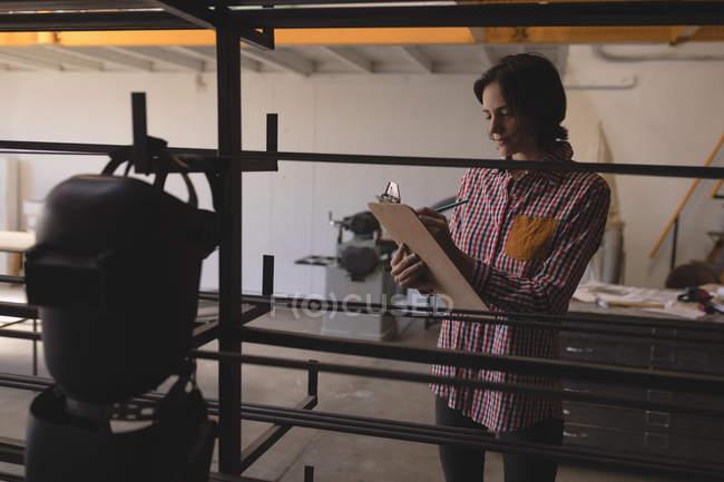 Mujer soldadora en portapapeles en taller de escritura. - foto de stock