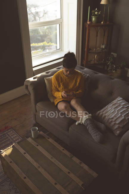 Woman using mobile phone in living room — Stock Photo