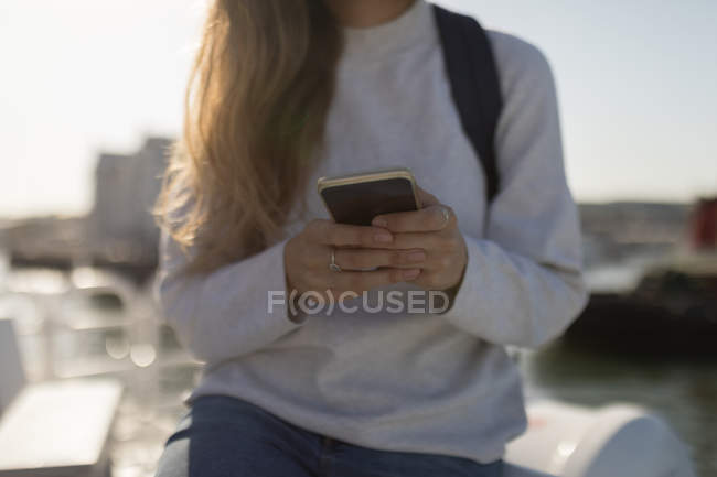 Mid section of woman using mobile phone on cruise ship — Stock Photo