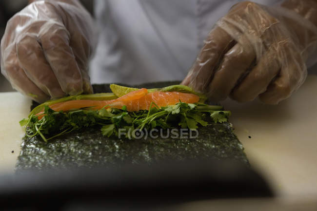 Mid section of senior chef preparing sushi in kitchen at restaurant — Stock Photo