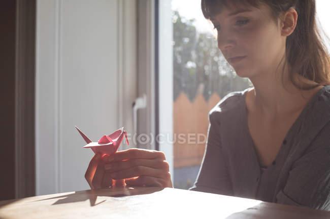 Frau schaut sich Papierbasteln zu Hause an — Stockfoto