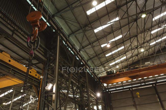 Низький кут зору металевий гачок, пов'язаних з ланцюга в майстерні — стокове фото