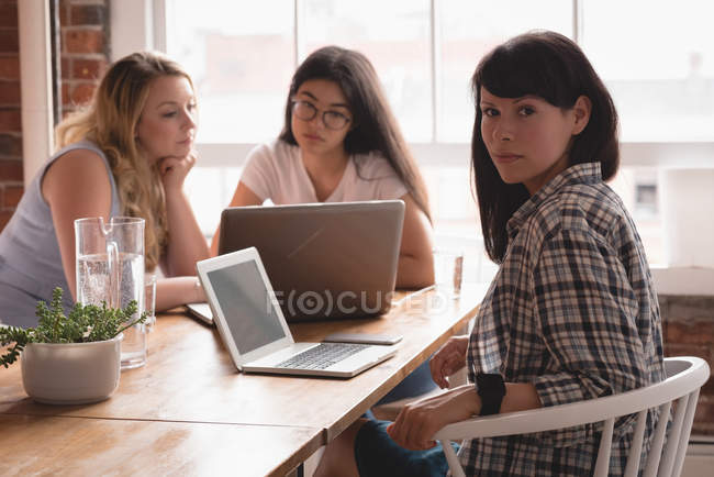 Female executive looking at camera while colleague discussing in the background at office — Stock Photo