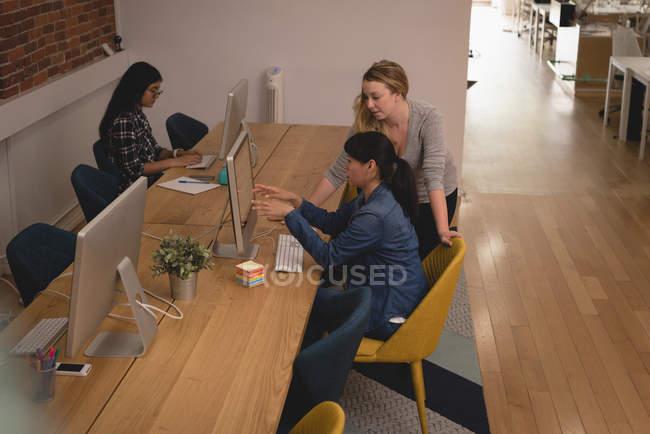 Жіночий керівників обговорювати над комп'ютером в офісі творчої — стокове фото