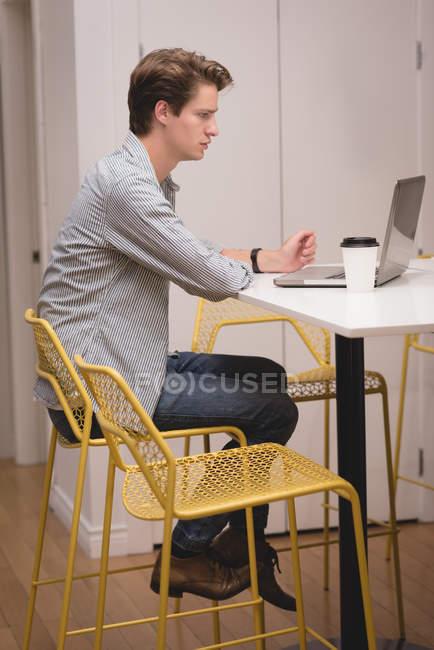 Мужчина, использующий ноутбук в офисе — стоковое фото