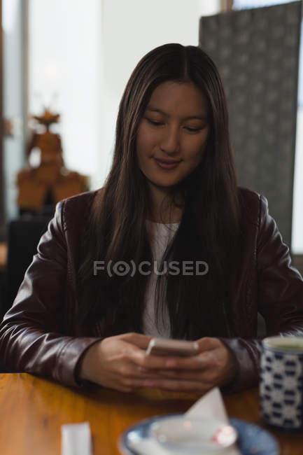 Mujer joven usando el teléfono móvil en el restaurante - foto de stock