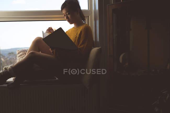 Frau liest ein Buch in der Nähe von Fenster zu Hause — Stockfoto