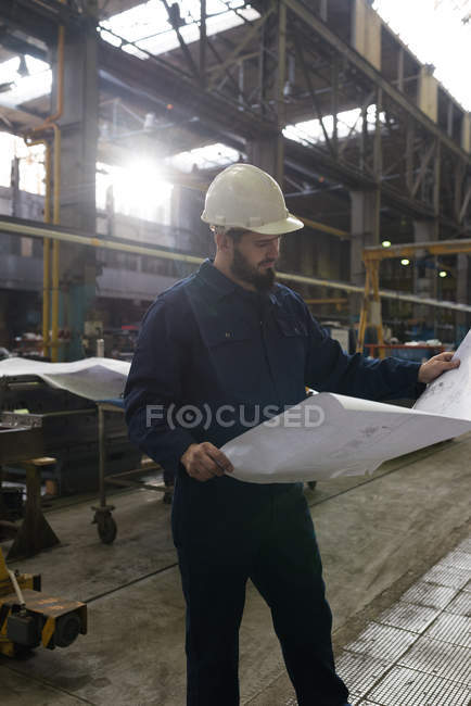 Technician looking at blue print in metal industry — Stock Photo