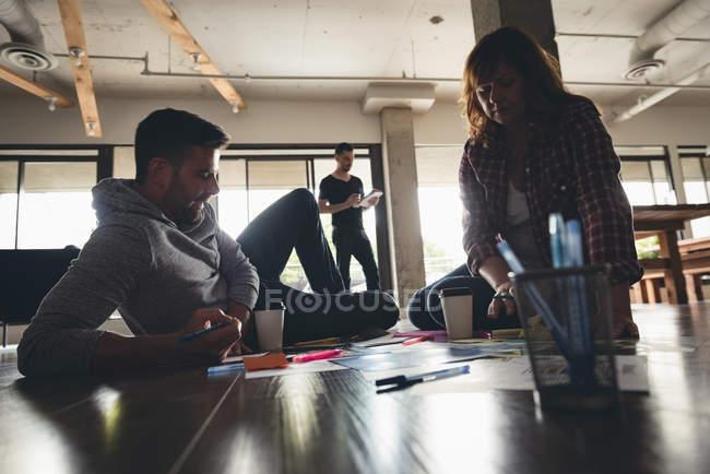 Деловые коллеги обсуждают документы в офисе — стоковое фото