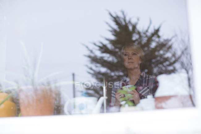 Beautiful mature looking through window at home — Stock Photo