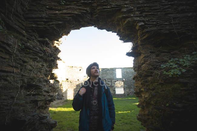Молодой турист-мужчина стоит у старых руин в сельской местности — стоковое фото