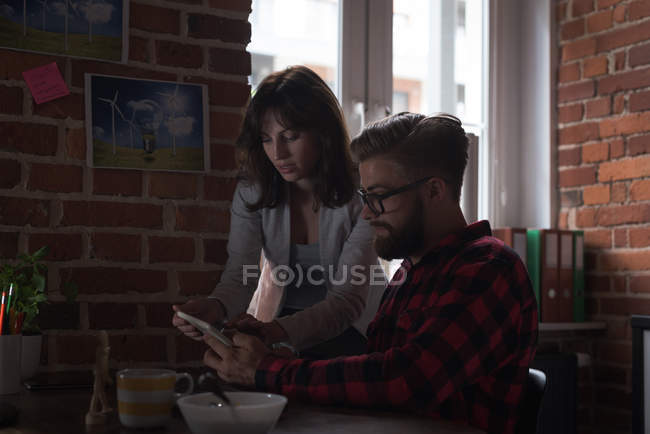 Male and female executives discussing over digital tablet in office — Stock Photo