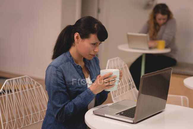 Female executive using laptop while having coffee in the creative office — Stock Photo