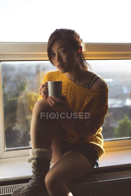 Woman having coffee near window at home — Stock Photo