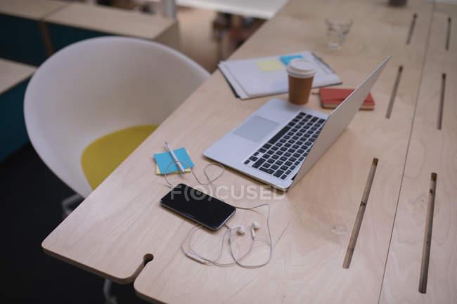 Ordinateur portable et téléphone portable sur un bureau au bureau — Photo de stock