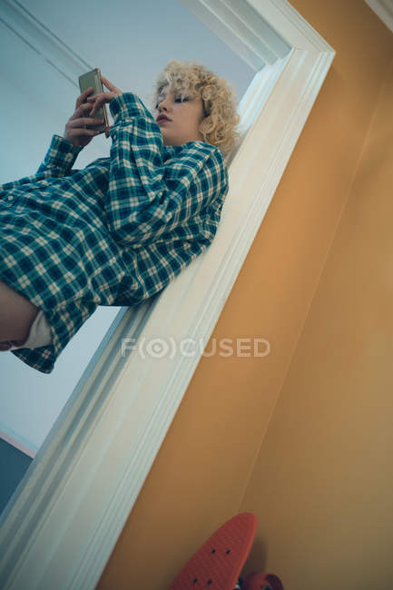 Woman using mobile phone near door at home — Stock Photo