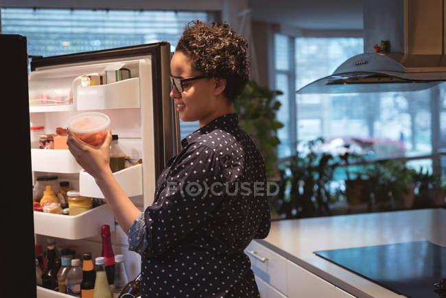 Joyeux jeune femme enceinte debout près du réfrigérateur à la recherche de nourriture dans la cuisine à la maison — Photo de stock