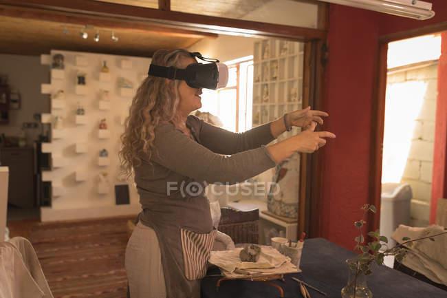 Oleiro feminino usando fone de ouvido realidade virtual em casa — Fotografia de Stock