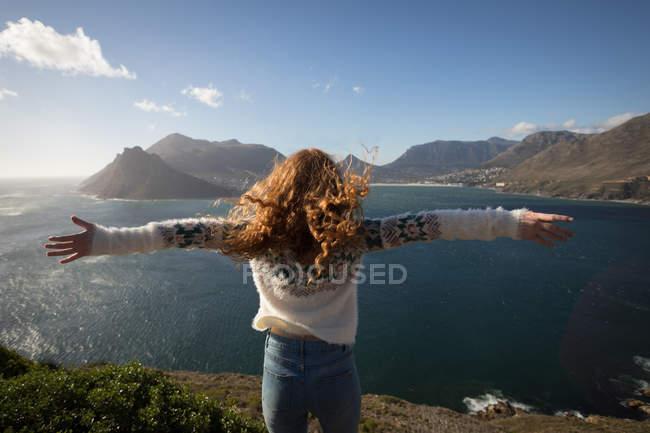Задній вид жінка з руки розкритими стоїть біля озера — стокове фото