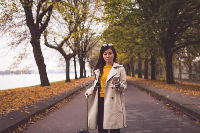 Businesswoman with mobile phone standing on street during autumn — Stock Photo