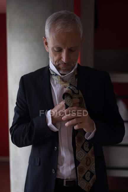 Homme d'affaires liant sa cravate dans la chambre d'hôtel — Photo de stock