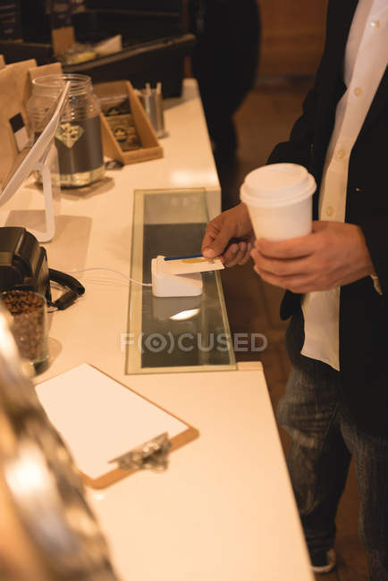 Mid section of man making NFC payment in coffee shop — Stock Photo
