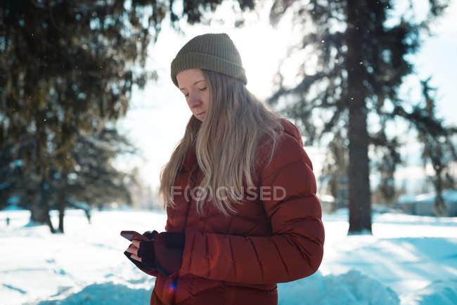 Donna in abbigliamento invernale utilizzando il telefono cellulare in una giornata di sole — Foto stock