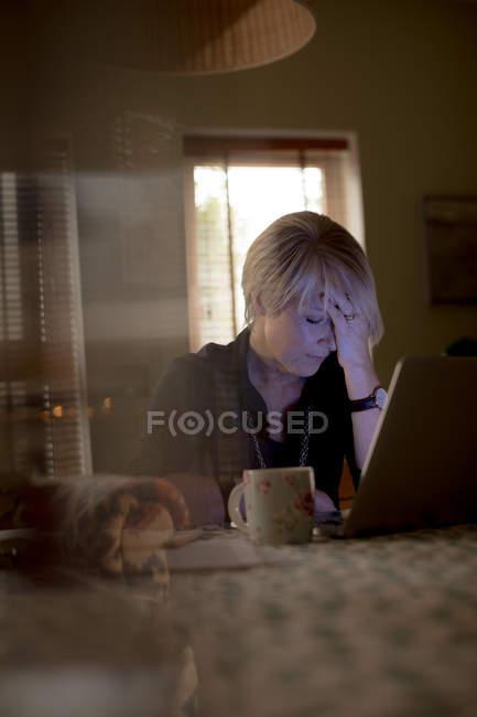 Mujer madura preocupada usando el ordenador portátil en la sala de estar en casa - foto de stock