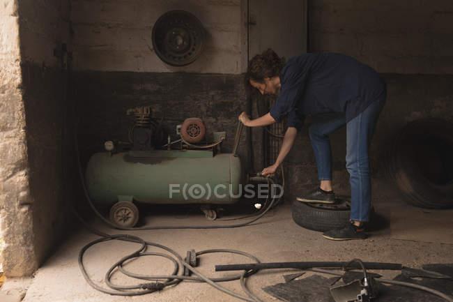 Trabajadora en la pintura de aerosol portátil máquina de taller - foto de stock