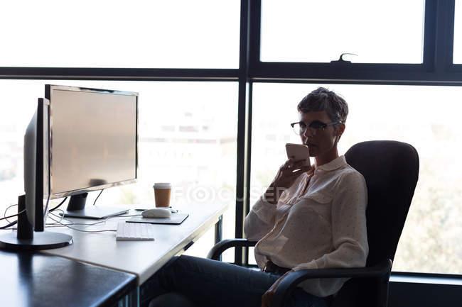 Donna d'affari matura che parla al cellulare mentre prende un caffè in ufficio — Foto stock