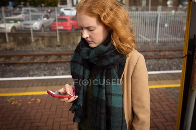 Jovem mulher usando seu telefone celular na plataforma ferroviária em um dia ensolarado — Fotografia de Stock