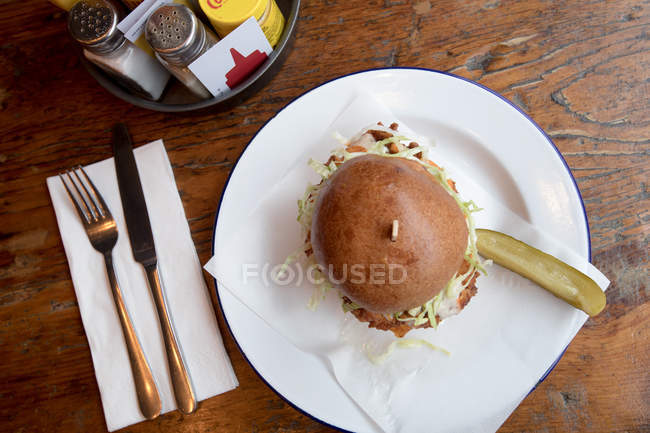 Top view of burger served in plate at restaurant with cutlery. — Stock Photo