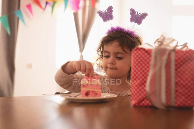 Маленькая девочка ест торт в гостиной дома . — стоковое фото