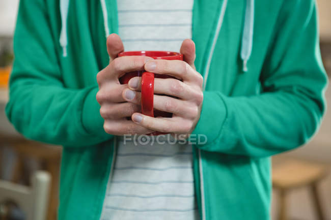 Mid section of man holding coffee mug at home — Stock Photo