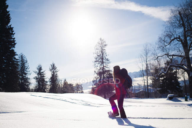 Woman walking on snowy slope on a sunny day — Stock Photo
