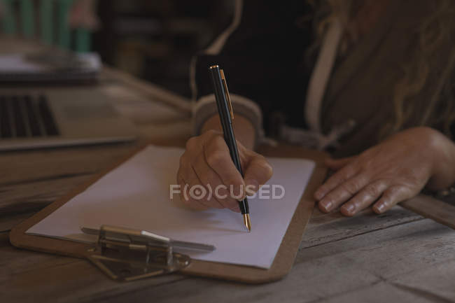 Close-up of mature woman writing on paper at home — Stock Photo