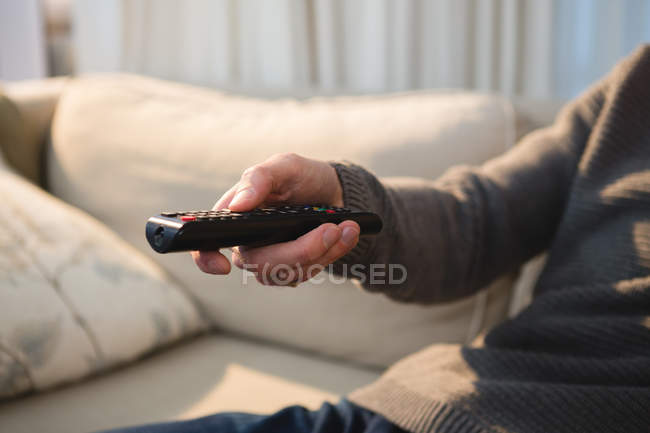 Средняя секция человека переключения канала с дистанционным управлением на дому — стоковое фото