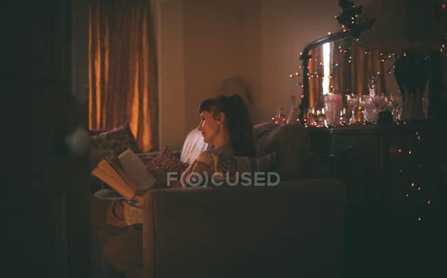 Женщина читает книгу в гостиной дома — стоковое фото