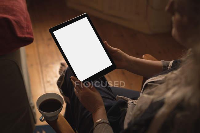 Mulher usando tablet digital enquanto toma café em casa — Fotografia de Stock
