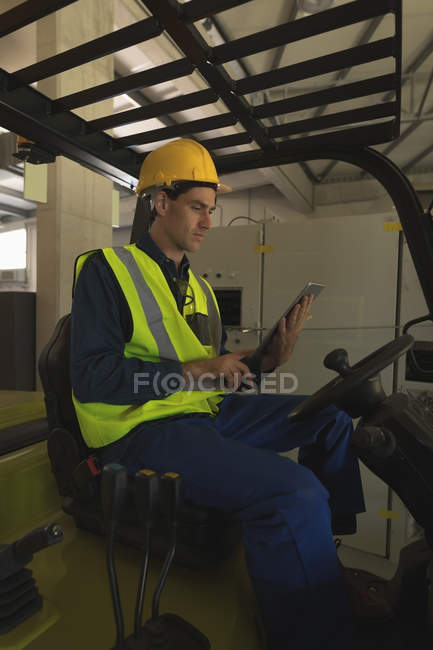 Male worker using digital tablet in forklift at solar station pant — Stock Photo