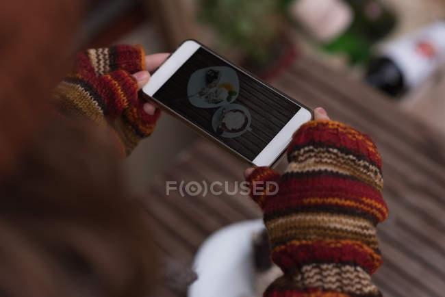 Жінка фотозйомка солодкої їжі з мобільного телефону в придорожньому кафе — стокове фото
