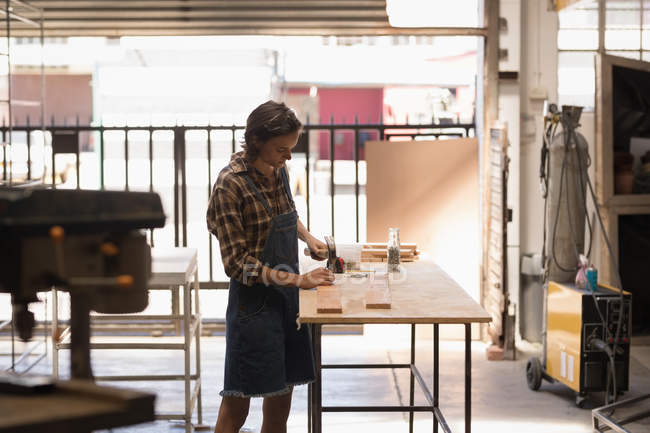 Young female artisan working in workshop. — Stock Photo
