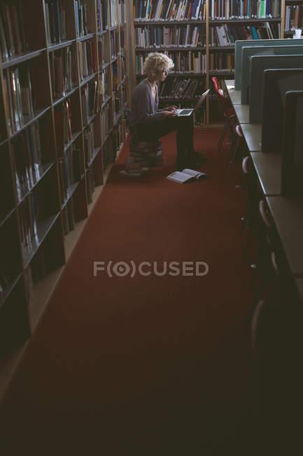 Jeune femme utilisant un ordinateur portable dans la bibliothèque — Photo de stock