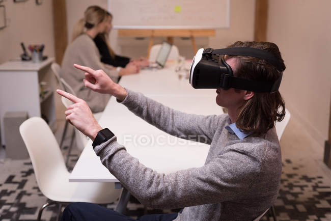 Male executive using virtual reality headset in office interior. — Stock Photo