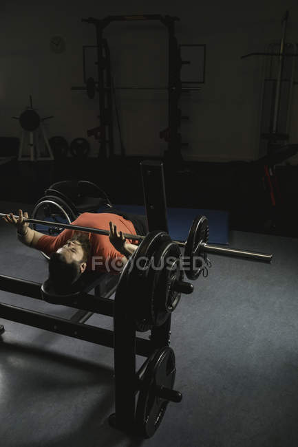 Handicapped man doing barbell bench pressing while exercising at fitness club — Stock Photo