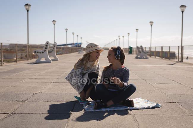 Happy siblings sitting on pavement near beach — Stock Photo